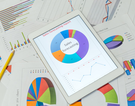printout: Financial charts on the table with tablet Stock Photo