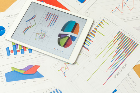 Financial charts on the table with tablet Stock Photo