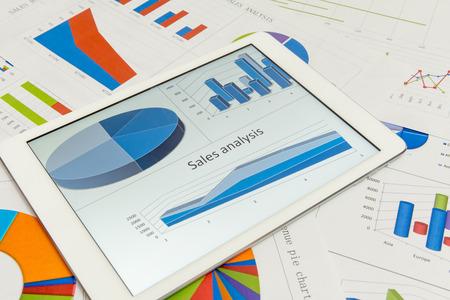 タブレットとテーブルの上の金融チャート 写真素材