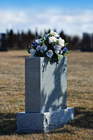 unmarked: Tombstone with bouquet of white and blue flowers