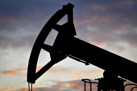 Oil pump jack on the sunset photo
