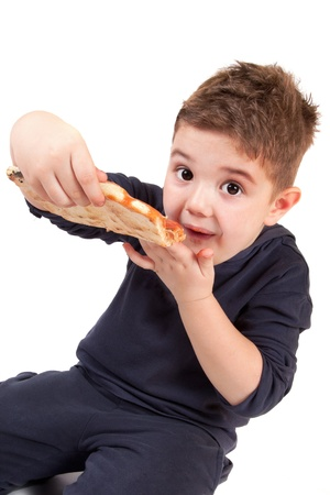 A young boy eating pizza photo