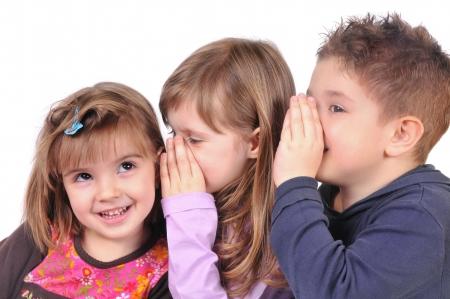 Two girls and a boy gossiping Standard-Bild