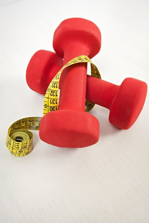 Dumbbell and measuring tape isolated on white photo