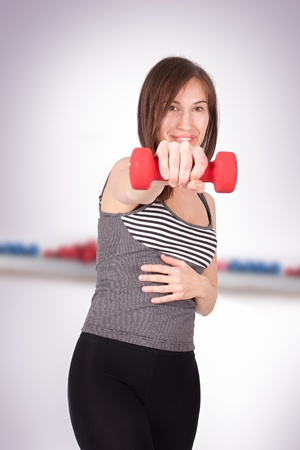 Woman with dumbbell in hand photo