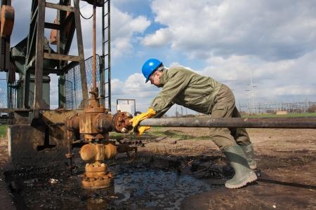 werknemer in de olie-industrie op oliepomp Stockfoto