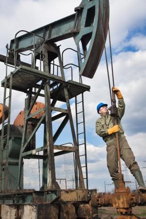 trabajador petroleros: de los trabajadores en la industria petrolera en la bomba de aceite Foto de archivo