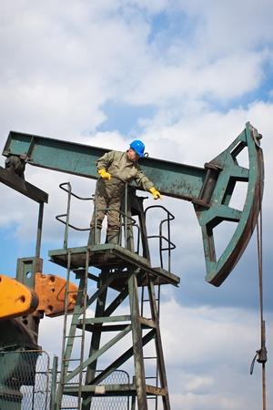 pozo petrolero: de los trabajadores en la industria petrolera en la bomba de aceite Foto de archivo