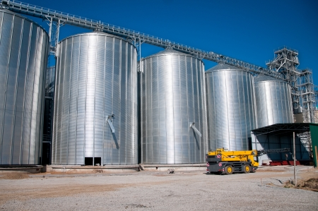 Silver Grain Silos with blue sky in background Stock Photo