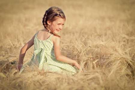 Cute happy girl walking in the field of wheat on sunny spring day photo