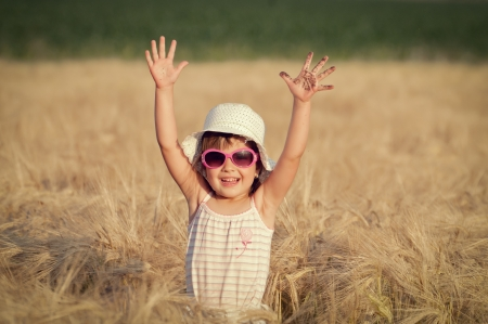 Happy girl in the field of wheat on sunny day Stock Photo - 13991616