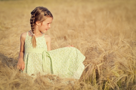 Happy girl in the field of wheat on sunny day photo