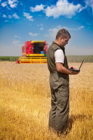 farm equipment: Farmer calculating earning in field
