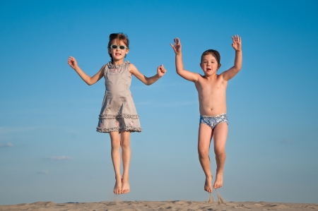 happy siblings jumping over sand photo