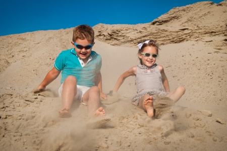 Little boy and girl playing in the sand photo