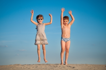 Photo of happy siblings jumping over sand photo