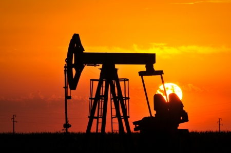 silhouetted: An oil pump jack is silhouetted by the setting sun