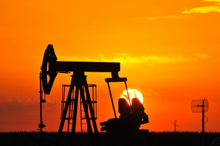 An oil pump jack is silhouetted by the setting sun Stock Photo - 14458886