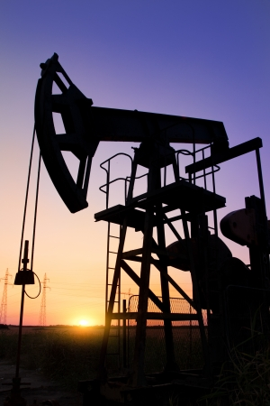 An oil pump jack is silhouetted by the setting sun photo