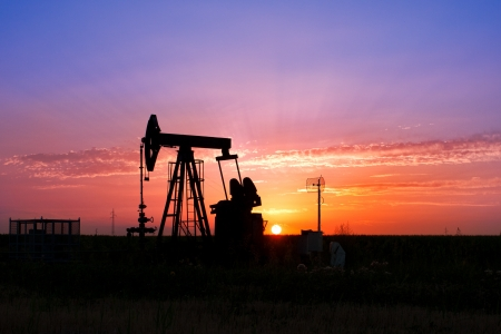 An oil pump jack is silhouetted by the setting sun Stock Photo - 14458901