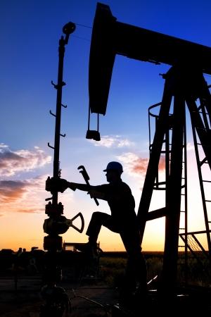 trabajador petroleros: T�cnica para el aceite en un paisaje Foto de archivo