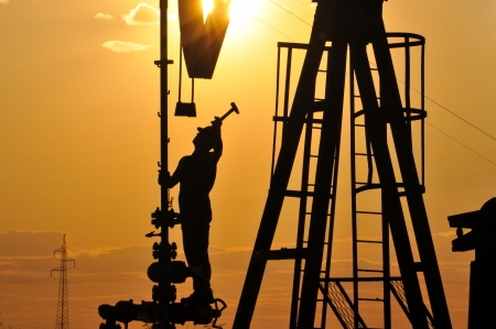silhouette of workers on oil rig