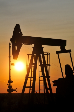 drilling well: Oil Pump on orange sunset