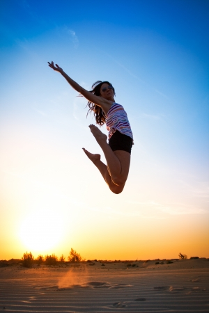 Young girl jumping in the sunset  photo