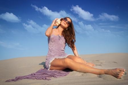 Beautiful woman on the seashore sand Stock Photo - 14605544