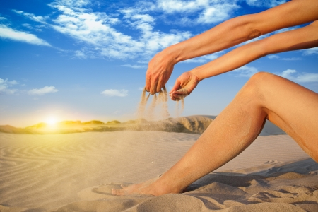Falling sand in woman hands photo