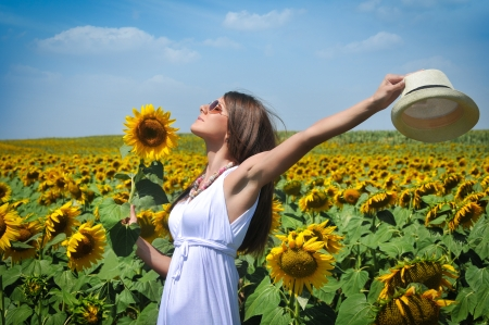 Young woman in beauty field with sunflowers photo