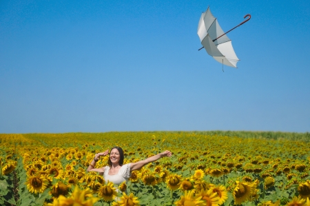 Young woman with umbrella on field in sunflower photo