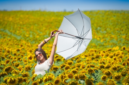 Young woman with umbrella on field in sunflower Stock Photo - 14774989