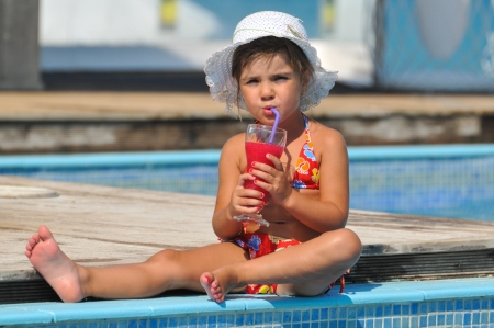 wading: girl sitting in the pool and drinking cocktails