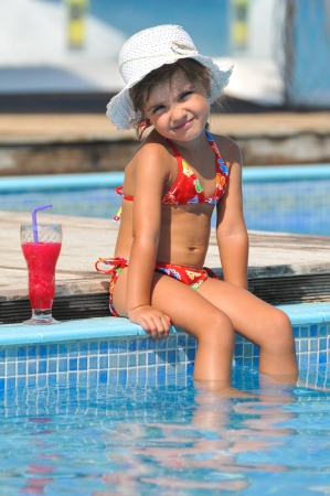 girl sitting in the pool and drinking cocktails photo