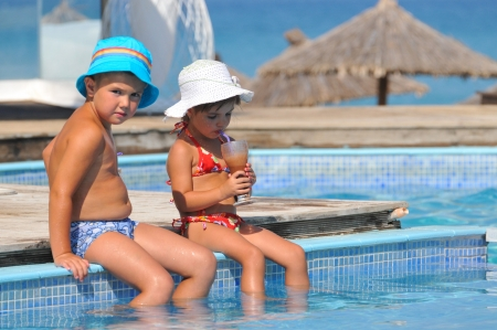 Little girl and boy sitting in the pool and drink photo