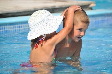 Smiling boy and little girl swimming in pool photo