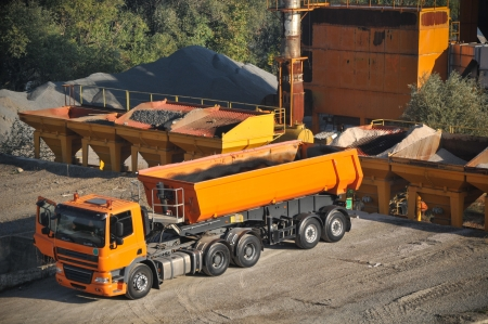 Orange truck in asphalt factory photo