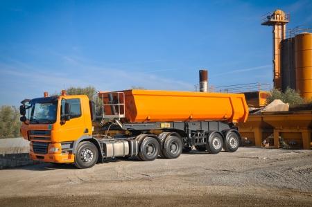 Oranje vrachtwagen in asfalt fabriek