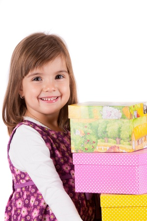Happy little girl with gifts against white background photo