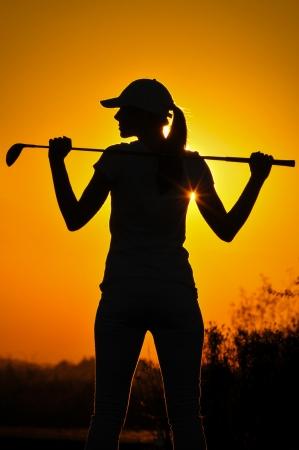 columpio: Jugador de golf femenino en la salida del sol Foto de archivo