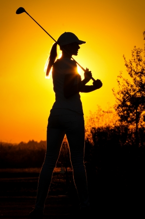 Female golfer at sunrise photo
