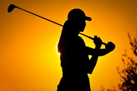 Vrouw golfspeler bij zonsopgang Stockfoto