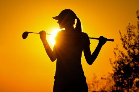 vrouw golfer tee-off tijdens silhouet zonsondergang Stockfoto