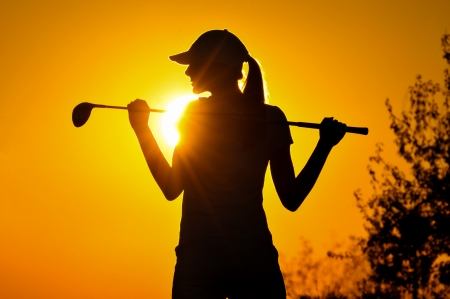 woman golf player tee off during sunset silhouetted Stock Photo - 15971514