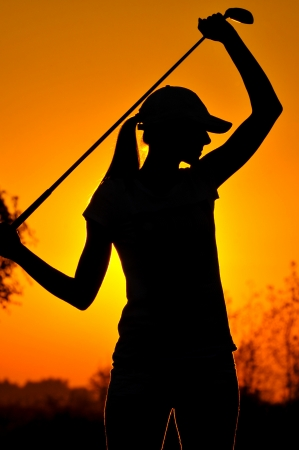 woman golf player tee off during sunset silhouetted photo