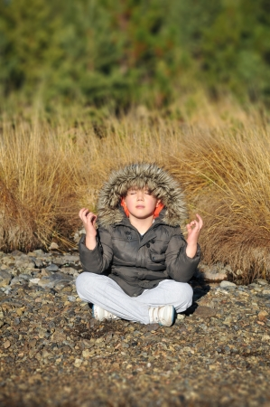 boy meditating on the bank of mountain river photo