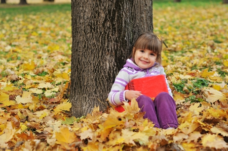 Girl playing in autumn park  photo