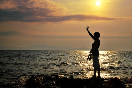 Young woman  standing on rock in sea and looking to somewhere photo