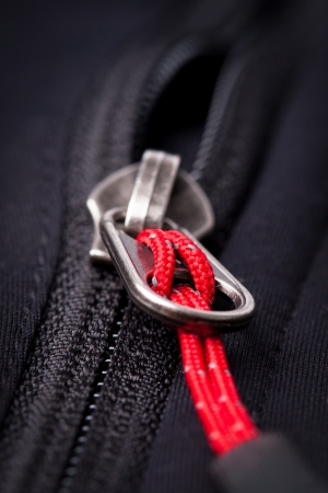 unbuttoned: metallic zipper over black background Stock Photo